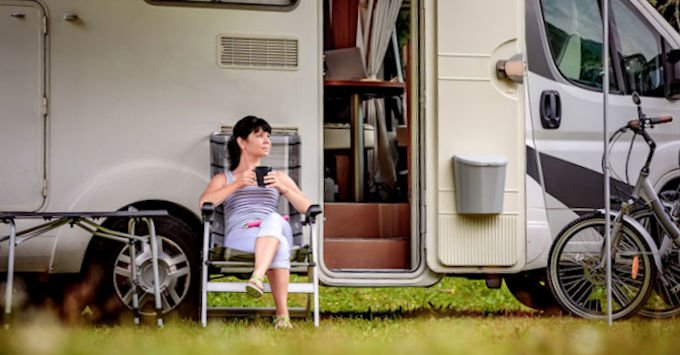 A lady sitting in front of her camper